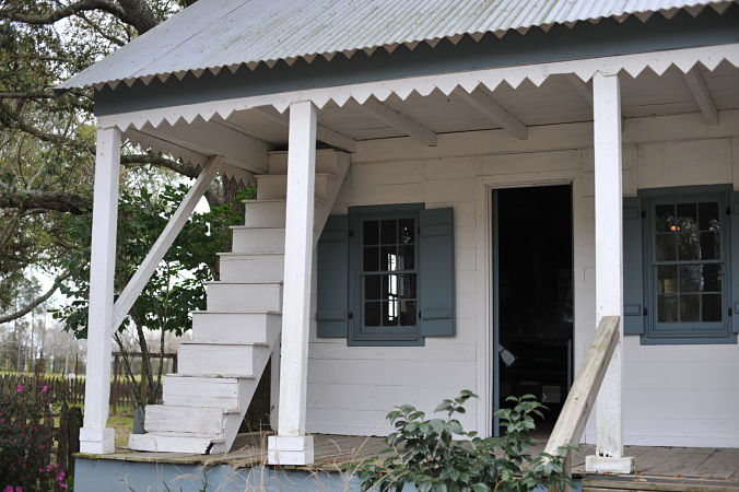 An example of an Acadian style house with stairs leading to the attic from the front porch