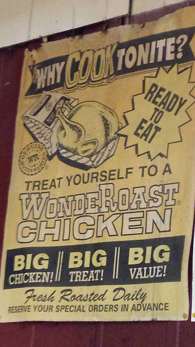The vintage rotisserie chicken sign right over the chicken rotisserie in the store.